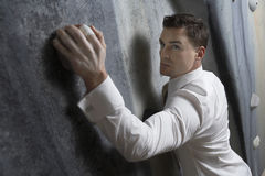 Serious Businessman Climbing Indoor Wall Royalty Free Stock Photo