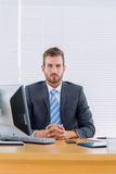 Serious businessman with computer at office desk Stock Images
