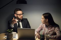 Serious businessman discussing with junior female manager at nig. Bearded mentor in glasses and suit explaining young female worker hard urgent problems in job Stock Image