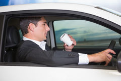 Serious businessman drinking coffee while driving Royalty Free Stock Images