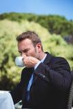 Serious businessman drinking coffee Stock Image