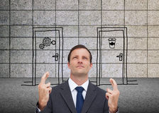 Serious businessman with fingers crossed is looking up Royalty Free Stock Photography