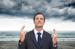 Serious businessman with fingers crossed is looking up Stock Image
