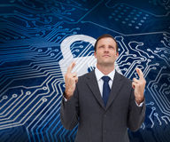 Serious businessman with fingers crossed is looking up Stock Images