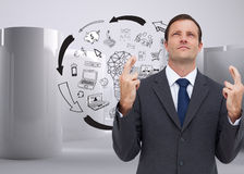 Serious businessman with fingers crossed is looking up Stock Photo