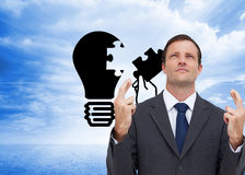 Serious businessman with fingers crossed is looking up Stock Photography