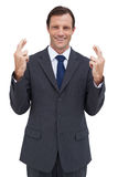 Serious businessman with fingers crossed stock photography