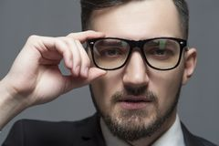 Serious businessman in formal suit and glasses. Close-up Serious businessman in formal suit and glasses looks at the camera on gray background. Place for text stock image