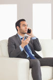 Serious businessman having a phone call sitting on cosy sofa Royalty Free Stock Photography