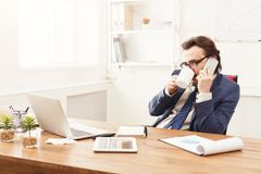 Serious businessman having phone talk. Serious businessman has mobile phone talk and having coffee at workplace in modern white office interior, copy space Stock Image