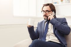 Serious businessman having phone talk. Serious businessman has mobile phone talk and having coffee, break in modern white office interior, copy space Royalty Free Stock Image