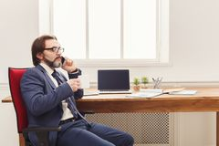 Serious businessman having phone talk. Serious businessman has mobile phone talk and having coffee at workplace in modern white office interior, side view, copy Royalty Free Stock Photo