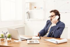 Serious businessman having phone talk. Serious businessman has mobile phone talk and having coffee at workplace in modern white office interior, copy space Royalty Free Stock Image