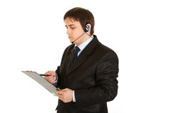 Serious businessman with headset checking notes Stock Photo