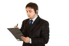 Serious businessman with headset and clipboard Stock Image