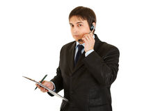 Serious businessman with headset and clipboard Stock Photos
