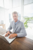 Serious businessman on his laptop looking at camera Royalty Free Stock Image