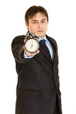 Serious businessman holding alarm clock in hand Royalty Free Stock Images