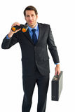 Serious businessman holding binoculars and a briefcase Royalty Free Stock Photography