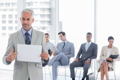 Serious businessman holding a blank notice. With people waiting behind stock image