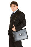 Serious businessman holding briefcase on shoulder Stock Image