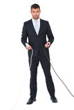 Serious businessman holding cables to connect Stock Image