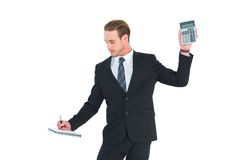 Serious businessman holding calculator taking notes Stock Photography