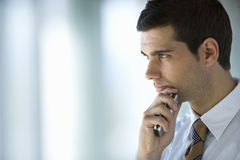 Serious businessman holding cell phone Stock Photo