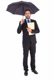 Serious businessman holding a file under umbrella Royalty Free Stock Photo