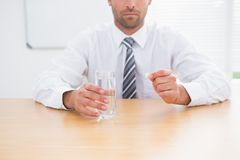 Serious businessman holding glass of water and tablet Royalty Free Stock Photography