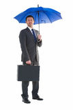 Serious businessman holding his umbrella and briefcase Royalty Free Stock Photo