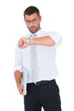 Serious businessman holding laptop checking time Stock Images