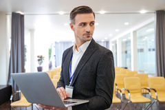 Serious businessman holding laptop in empty meeting hall. Portrait of serious attractive businessman standing and holding laptop in empty meeting hall Stock Images
