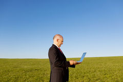 Serious Businessman Holding Laptop On Field Stock Images