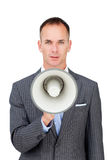 Serious businessman holding a megaphone Stock Images