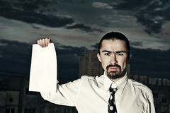 Serious businessman holding a sheet of paper Royalty Free Stock Photo
