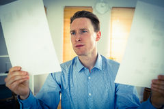 Serious businessman holding two paper sheets Stock Photography