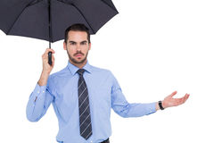 Serious businessman holding umbrella with arm out Stock Photo
