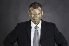 Serious businessman with jungle camouflage paint Royalty Free Stock Photography