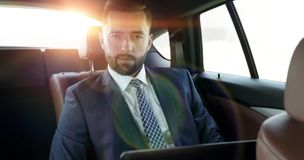 Businessman with laptop sitting in a comfortable car. Serious businessman with laptop sitting in a comfortable car Stock Photography