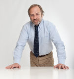 Serious businessman leaning on a table Stock Images