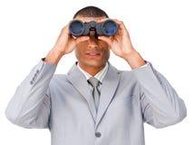 Serious businessman looking through binoculars Royalty Free Stock Images
