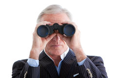 Serious businessman looking through binoculars. Standing against a white background Stock Photography