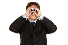 Serious businessman looking through binoculars. Serious young businessman looking through binoculars isolated on white Royalty Free Stock Photos