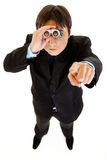 Serious businessman looking through binoculars. And pointing finger at you isolated on white Stock Photo