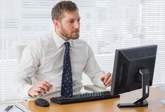 Serious businessman looking at computer Stock Images