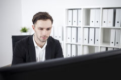 Serious businessman looking at computer screen Royalty Free Stock Image