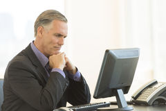 Serious Businessman Looking At Desktop PC In Office Royalty Free Stock Image
