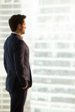 Serious businessman lost in thoughts standing looking at city bu. Serious confident businessman wearing blue suit standing in office looking at city buildings Stock Photography