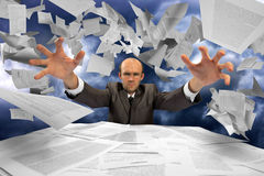 Serious businessman manipulating papers. Against dramatic blue sky Royalty Free Stock Photo